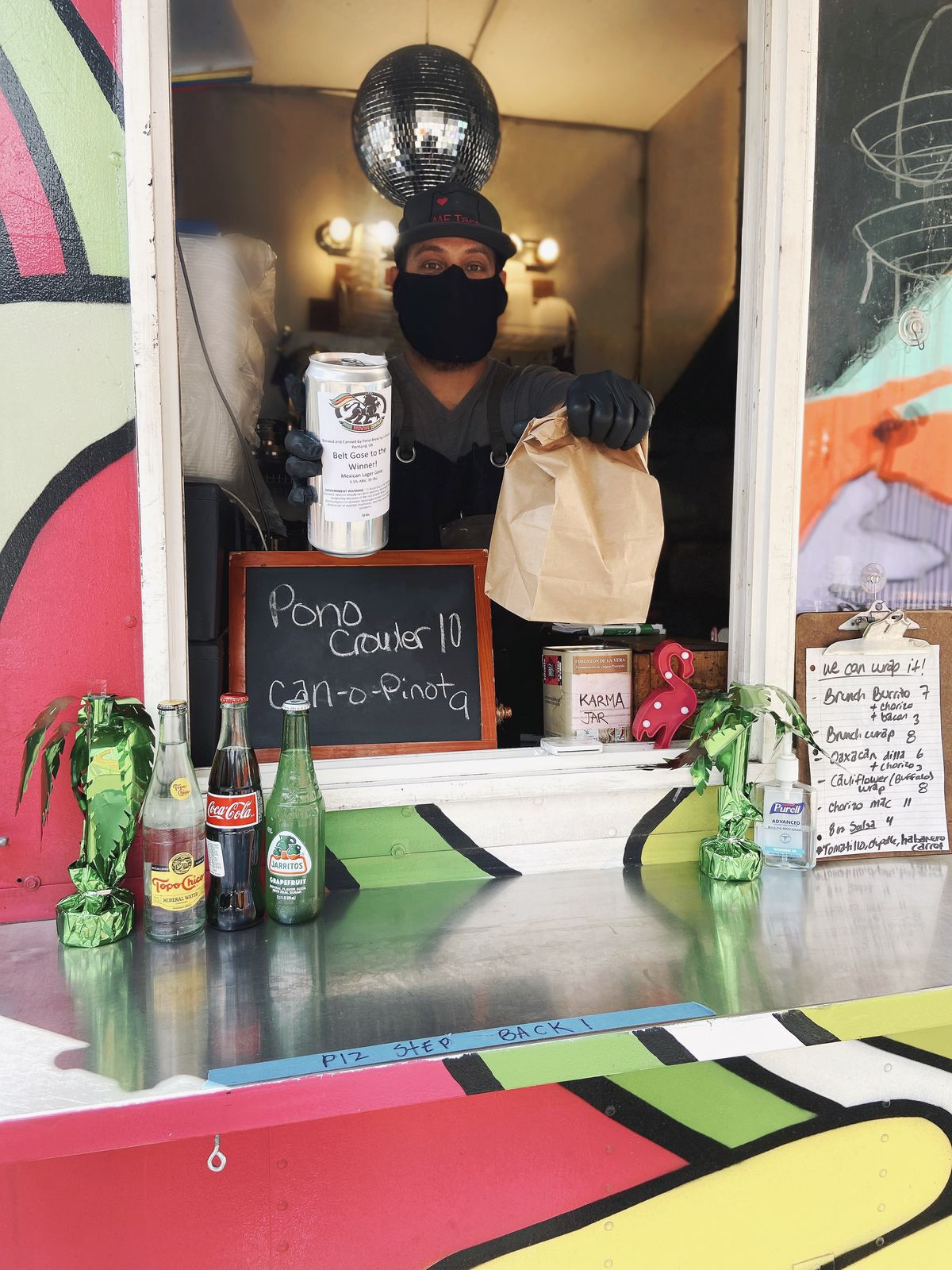 A man in a baseball cap, black face mask, and black gloves holds a beer and a paper bag from the inside of a food cart. A disco-ball hangs over his head.