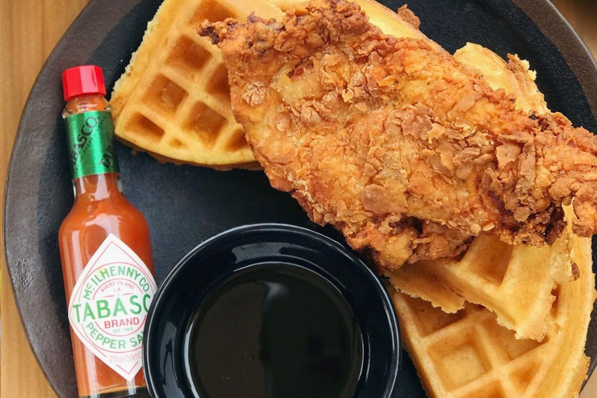 A serving of fried chicken and waffles on a plate with Tabasco sauce, syrup, and butter