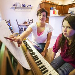 Piano teacher and stay-at-home mom Liana Sorenson works with Gwen Robertson at her home in Heber on Tuesday, Nov. 24, 2015.