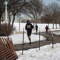 People walk along the lakefront near a portion of West Montrose Avenue east of Lake Shore Drive that had been closed since March amid fears of the coronavirus pandemic, Tuesday, Feb. 23, 2021. The Chicago Park District announced plans Tuesday to gradually reopen the city's lakefront, playgrounds and indoor swimming pools in response to sustained declines in COVID-19 positivity rates and cases.
