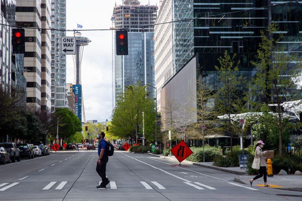 Pedestrians on a downtown Seattle street stroll through a crosswalk wearing masks