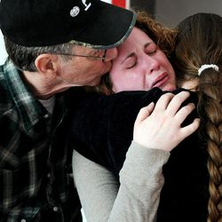 In this April 4, 2012 photo, an emotional Juliane White, center, gets a hug from her mother, Ann, and a kiss from her father, O. T. Green, in her new home in Lakeside, Mont. White's husband, Kevin, died in his sleep on Sunday, April 1, just two weeks before they were scheduled to move in.