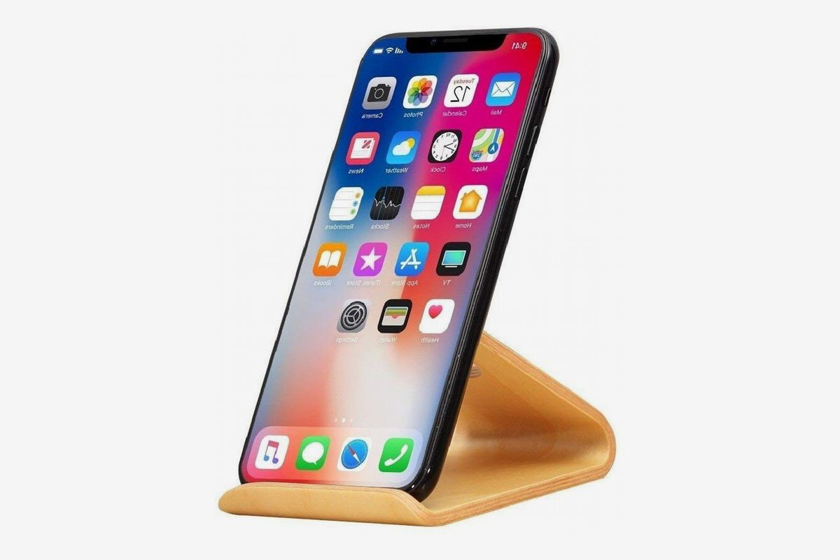 Wooden stand holds up a smartphone.