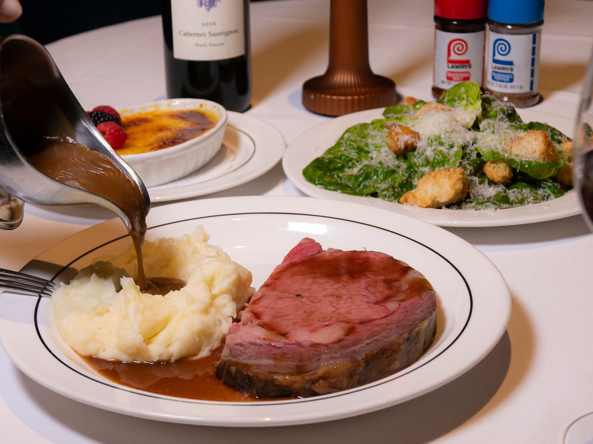 A plate of mashed potatoes and prime with a salad in the background