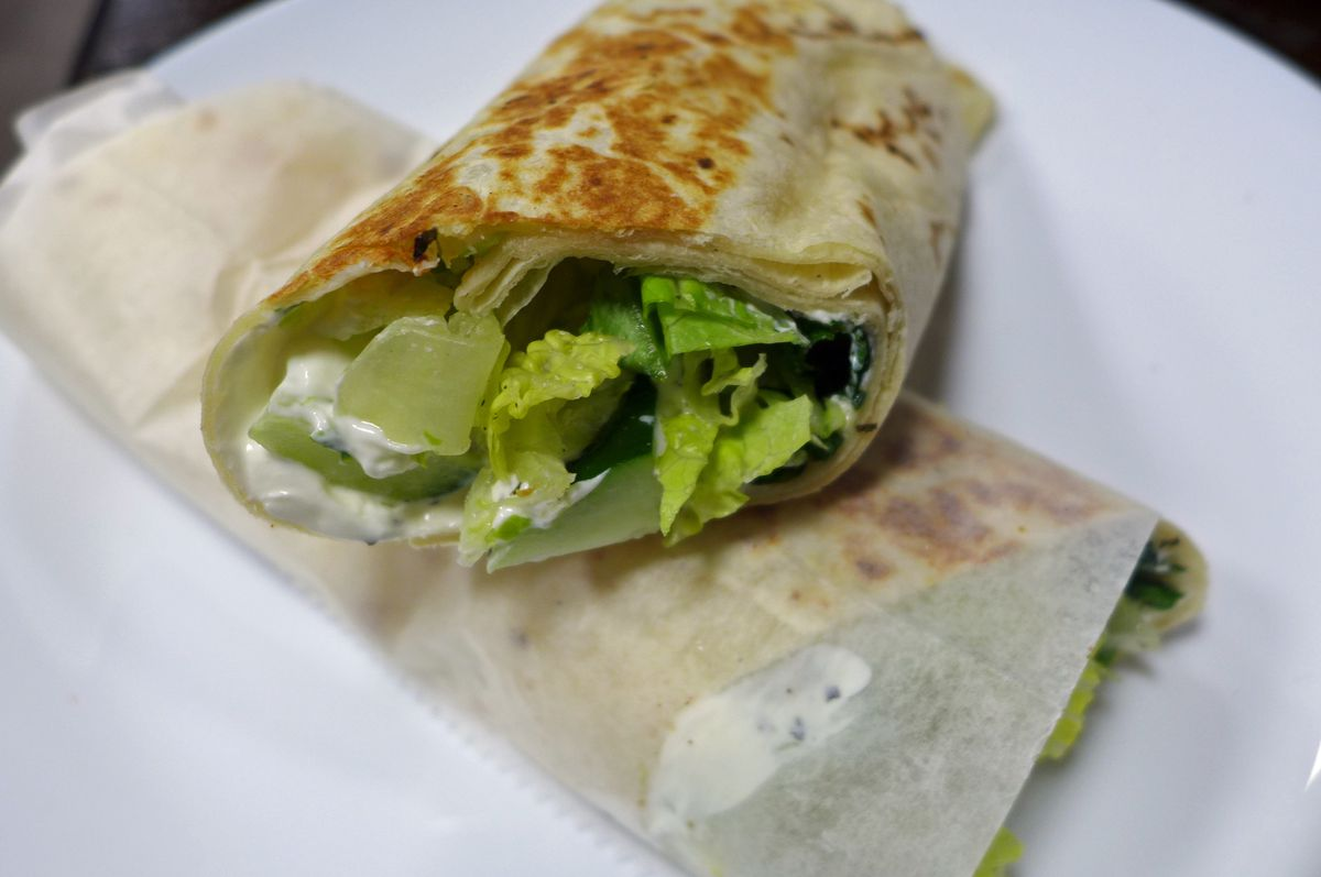 Yogurt and greenery rolled into a pita and cut in two showing the sandwich in cross section.