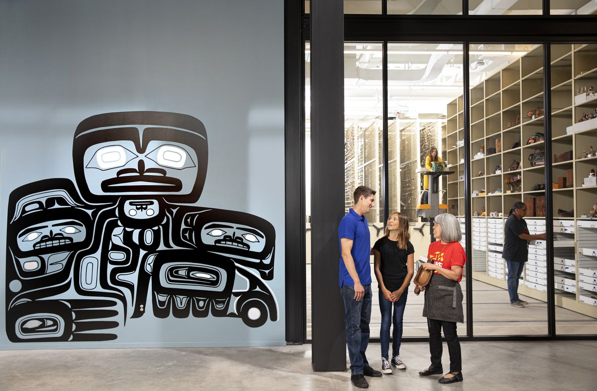 A slate blue wall with a traditional Coast Salish design is on a wall to the left. To the right, floor-top-ceiling windows showing a series of shelves. In front, three people stand in a circle talking.
