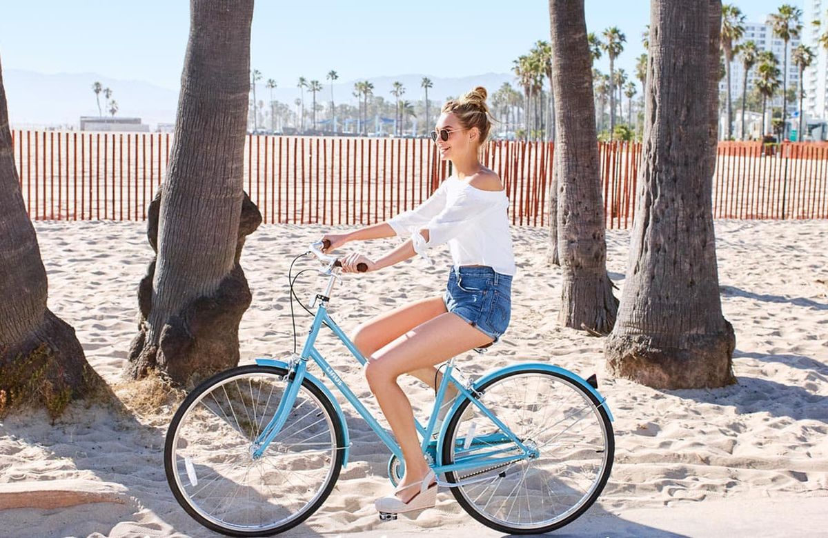 A woman in denim shorts and a white shirt riding a bike on the beach
