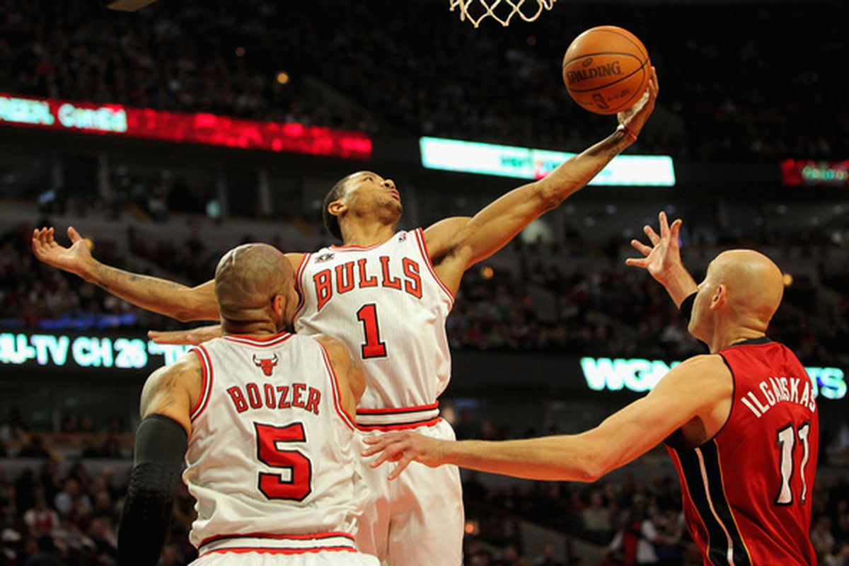 Derrick Rose of the Chicago Bulls collects a rebound inf ront of Carlos Boozer of the Bulls and Zydrunas Ilgauskas of the Miami Heat at the United Center in Chicago Illinois. (Photo by Doug Pensinger/Getty Images)