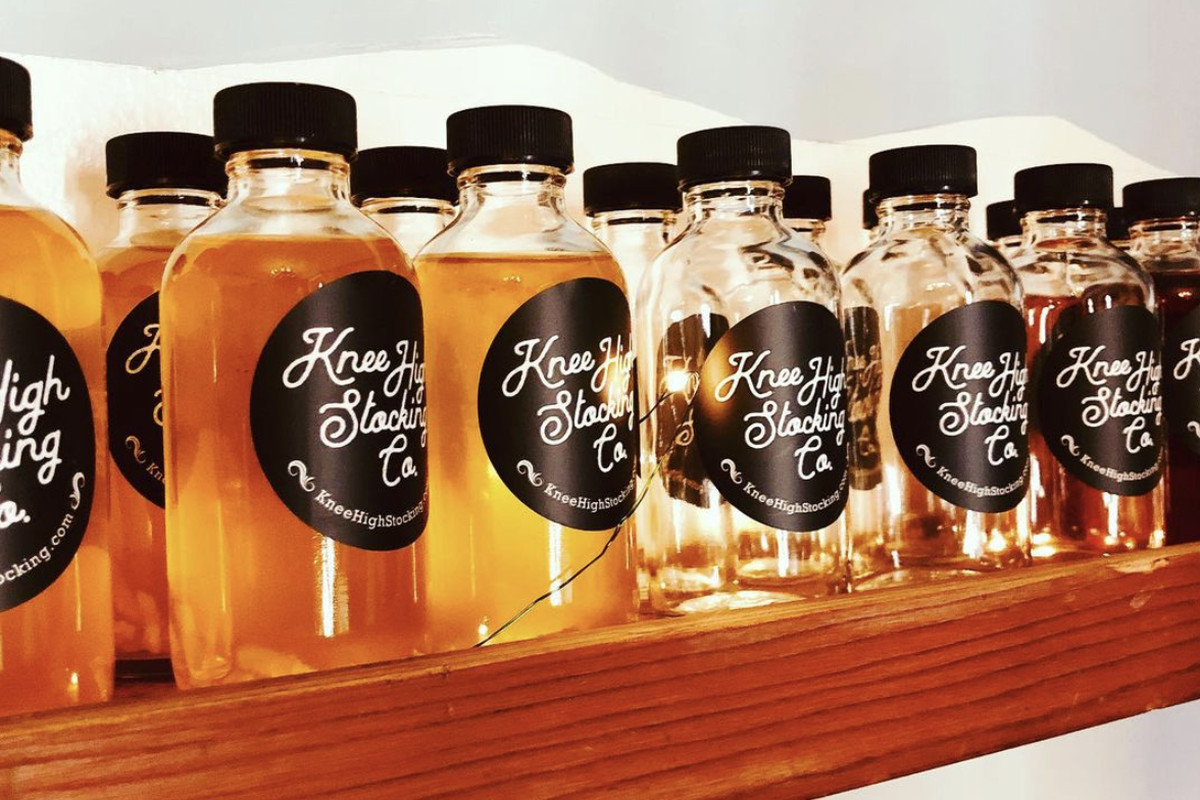 A row of small bottles on a shelf filled with brownish liquor, all labeled with the logo for Knee High Stocking Co.