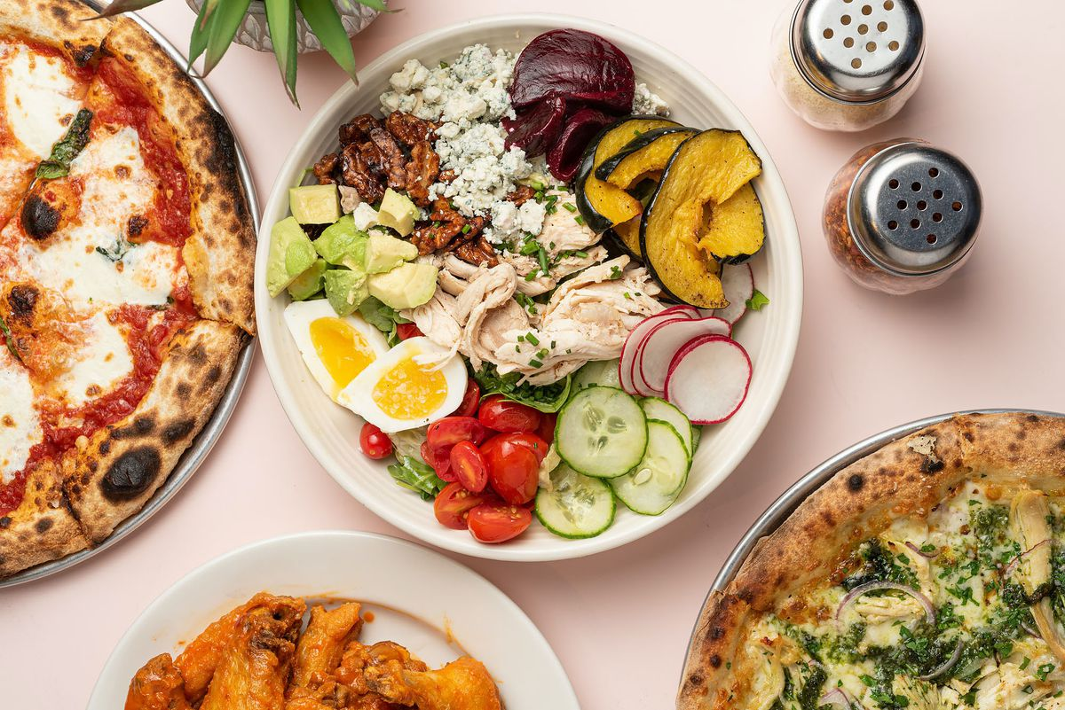Pizza, salad, and sides on a light pink table.