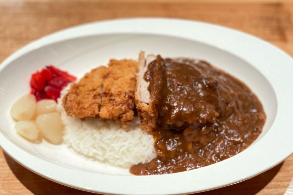 A plate of katsu curry: Crispy breaded fried pork on the left; dark, rich beef-based curry gravy on the right