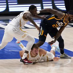 Dallas Mavericks forward Dorian Finney-Smith, left, Luka Doncic, center, and Utah Jazz forward Royce O'Neale, right, all compete for control of the ball after Doncic lost it on the dribble in the first half of an NBA basketball game in Dallas, Monday, April 5, 2021.