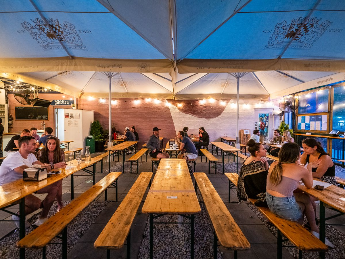 Customers at beer garden Dacha leave every other table empty
