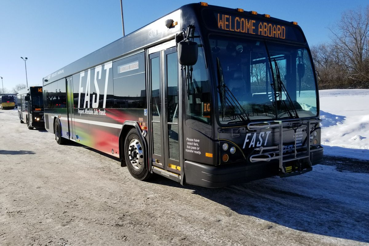 """A black bus with """"FAST"""" written on the side and """"Welcome Aboard"""" on a screen above the white window."""