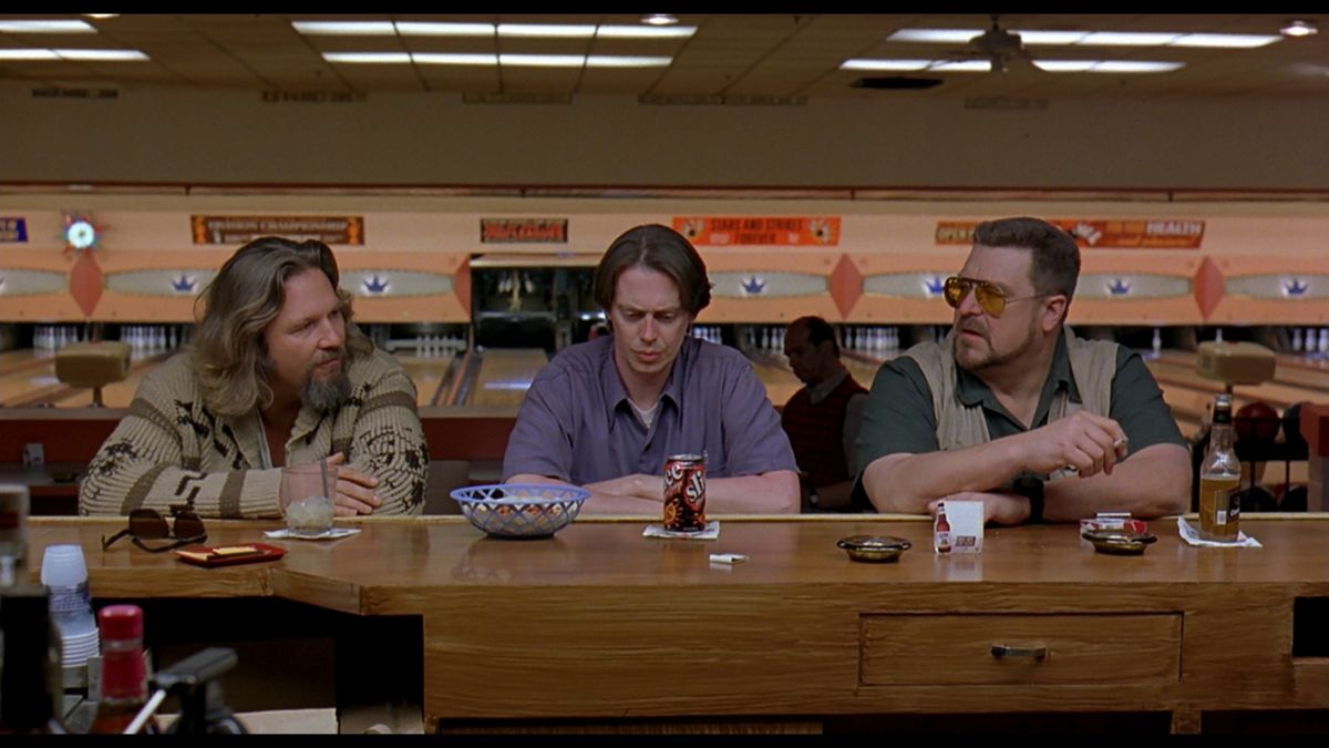 three men sitting at a bowling alley counter