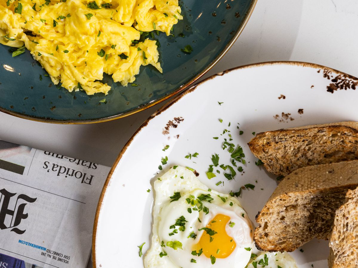two plates topped with eggs on a table
