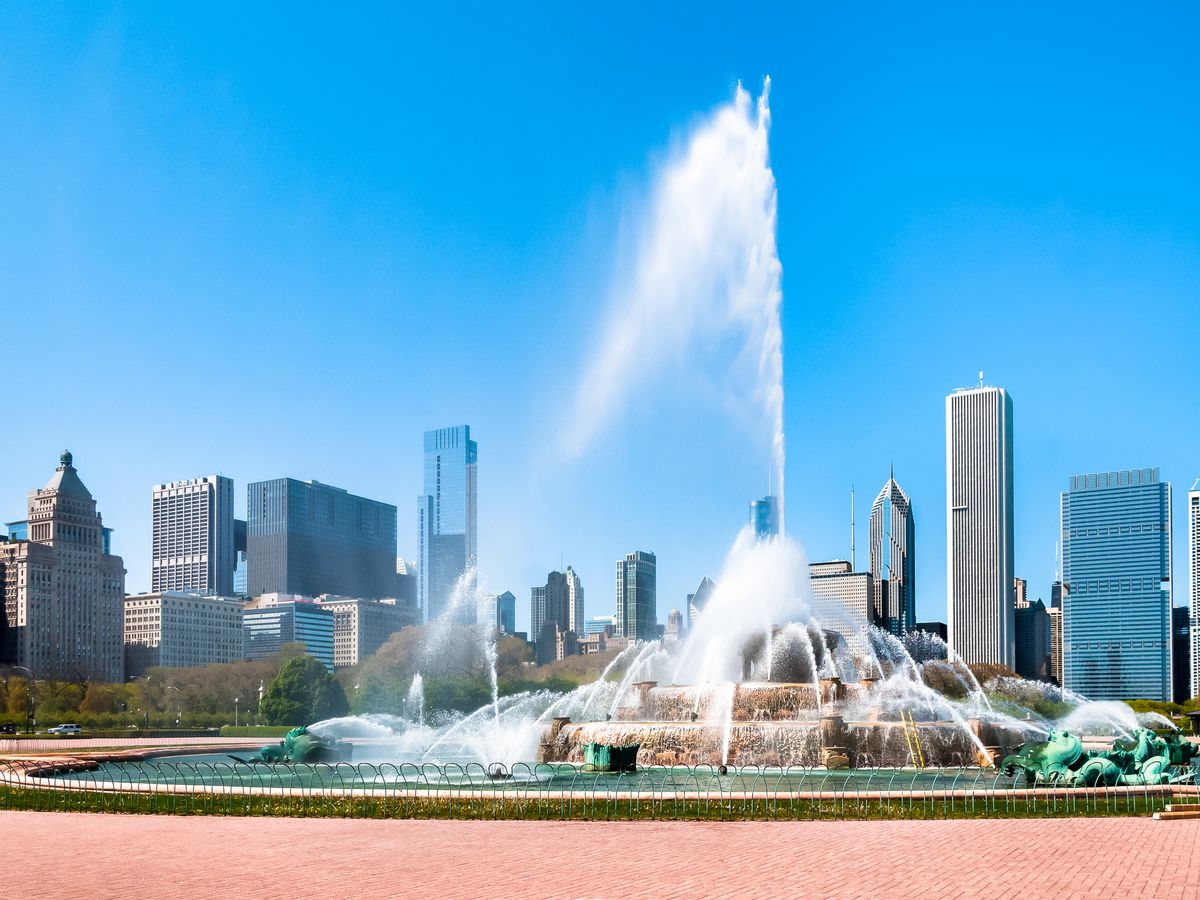 A water fountain in a courtyard in Chicago. In the distance are the tall city buildings of the Chicago skyline.