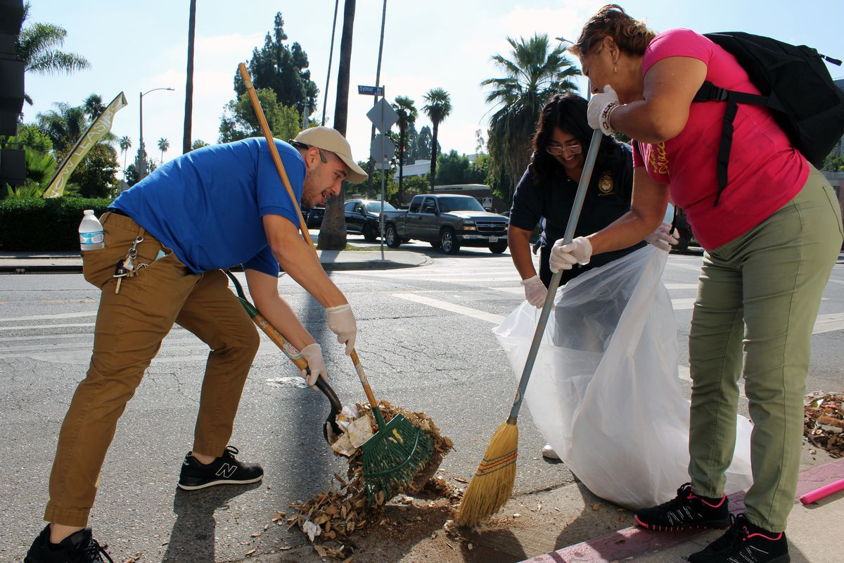 A group of three sweeping the side of a street in Van Nuys.
