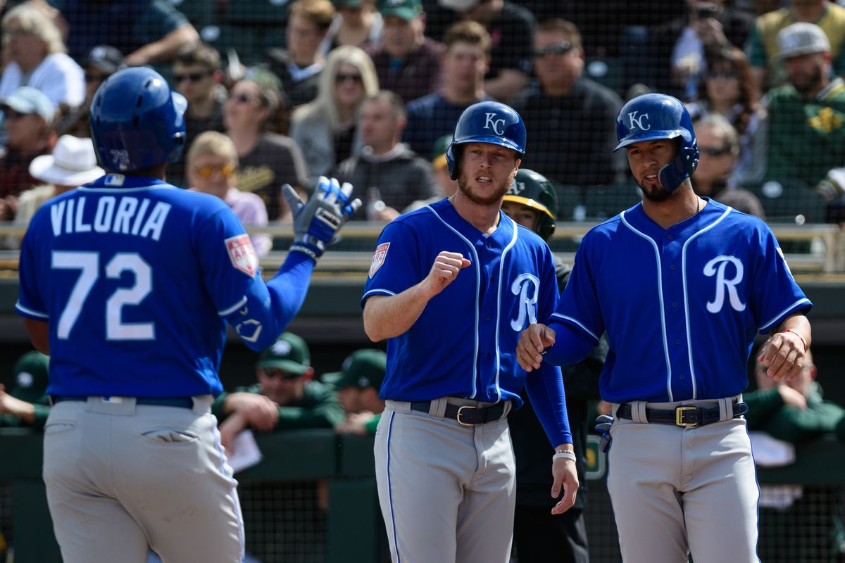 Meibrys Viloria #72 of the Kansas City Royals is congratulated by Brett Phillips #14 and Cheslor Cuthbert #19 after hitting a three run homer in the first inning against the Oakland Athletics at HoHoKam Stadium on February 24, 2019 in Mesa, Arizona.