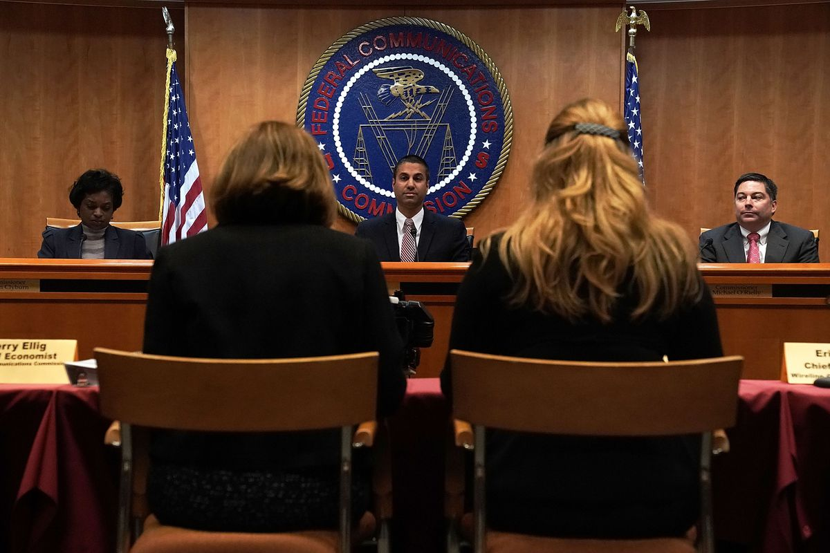 Federal Communications Commission Chairman Ajit Pai (C) and commission members Mignon Clyburn (L) and Michael O'Rielly (R)sit at their bench in front of the FCC plaque.