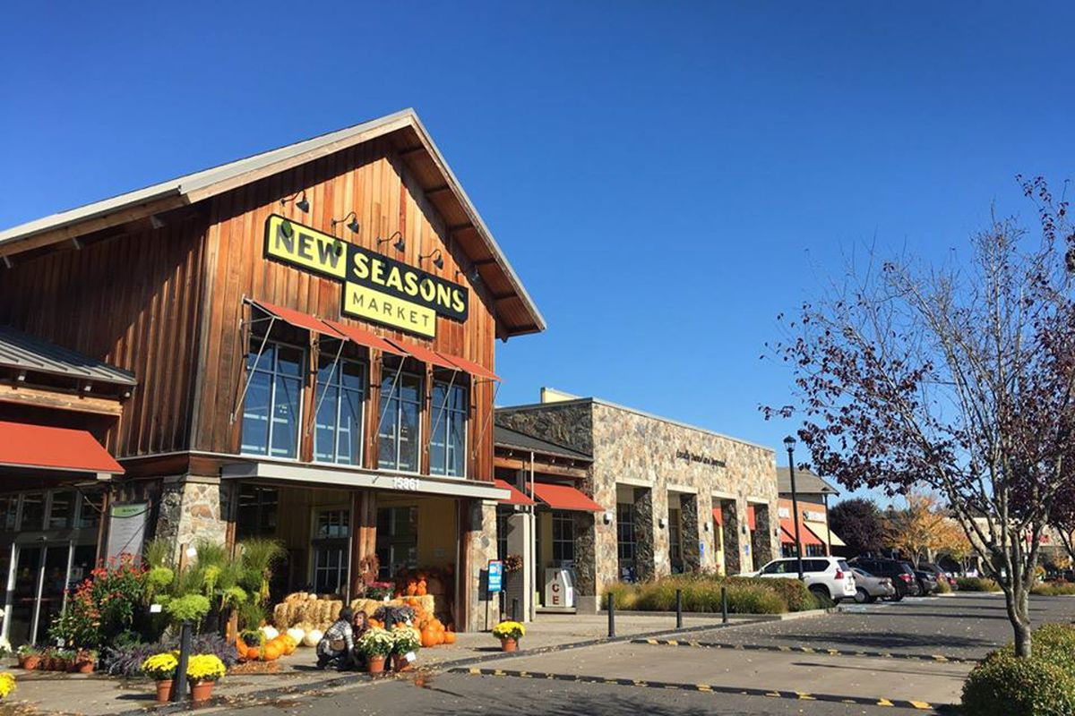 A picture of a New Seasons location with wooden paneling and an autumnal outdoor display