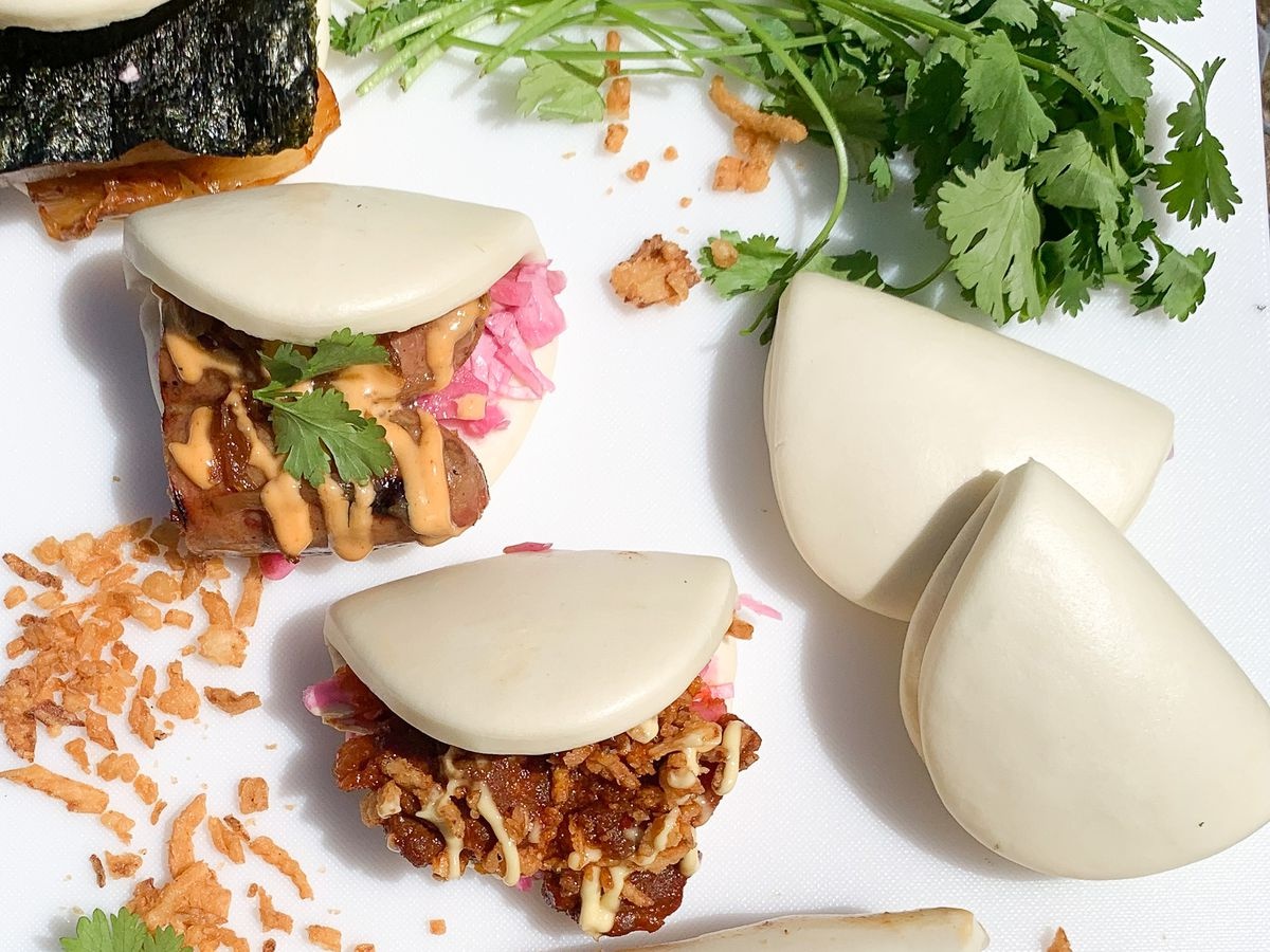 A bunch of empty and stuffed bao spread across a white background.