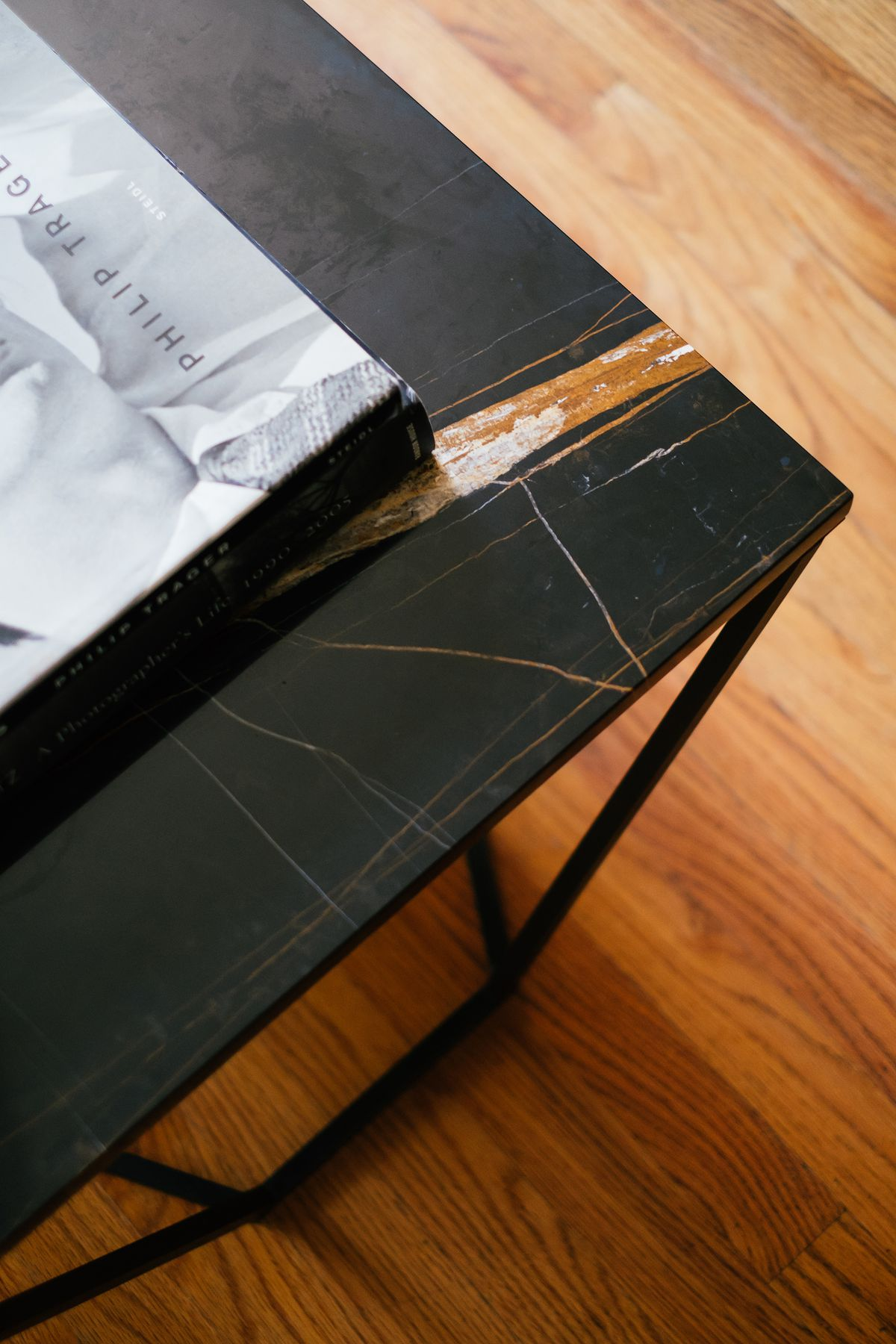 A detail showing the corner of a coffee table with a black metal base and a black marble surface.