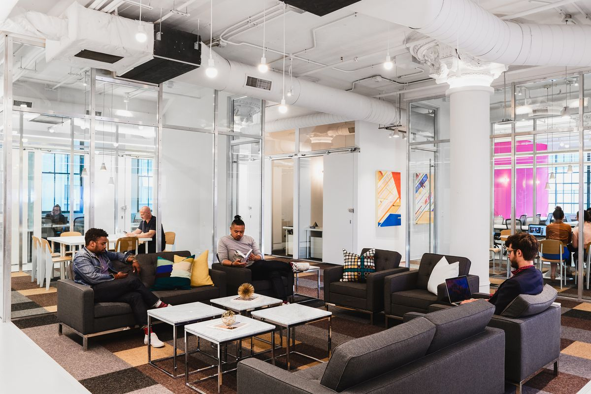 A coworking space with exposed, white ductwork and pillars, and big industrial-sized windows.