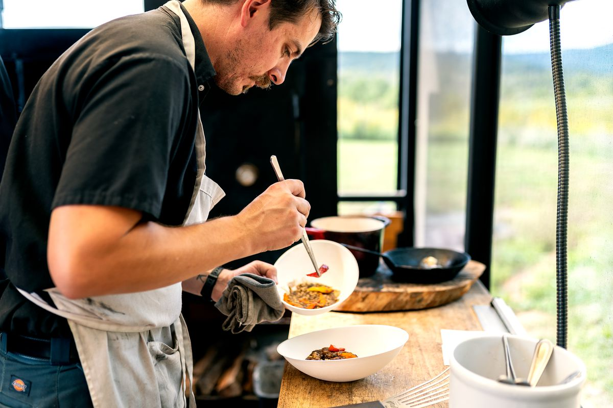 A mustachioed chef in an apron uses tweezers to plate a dish sitting on a wooden countertop inside an open trailer.