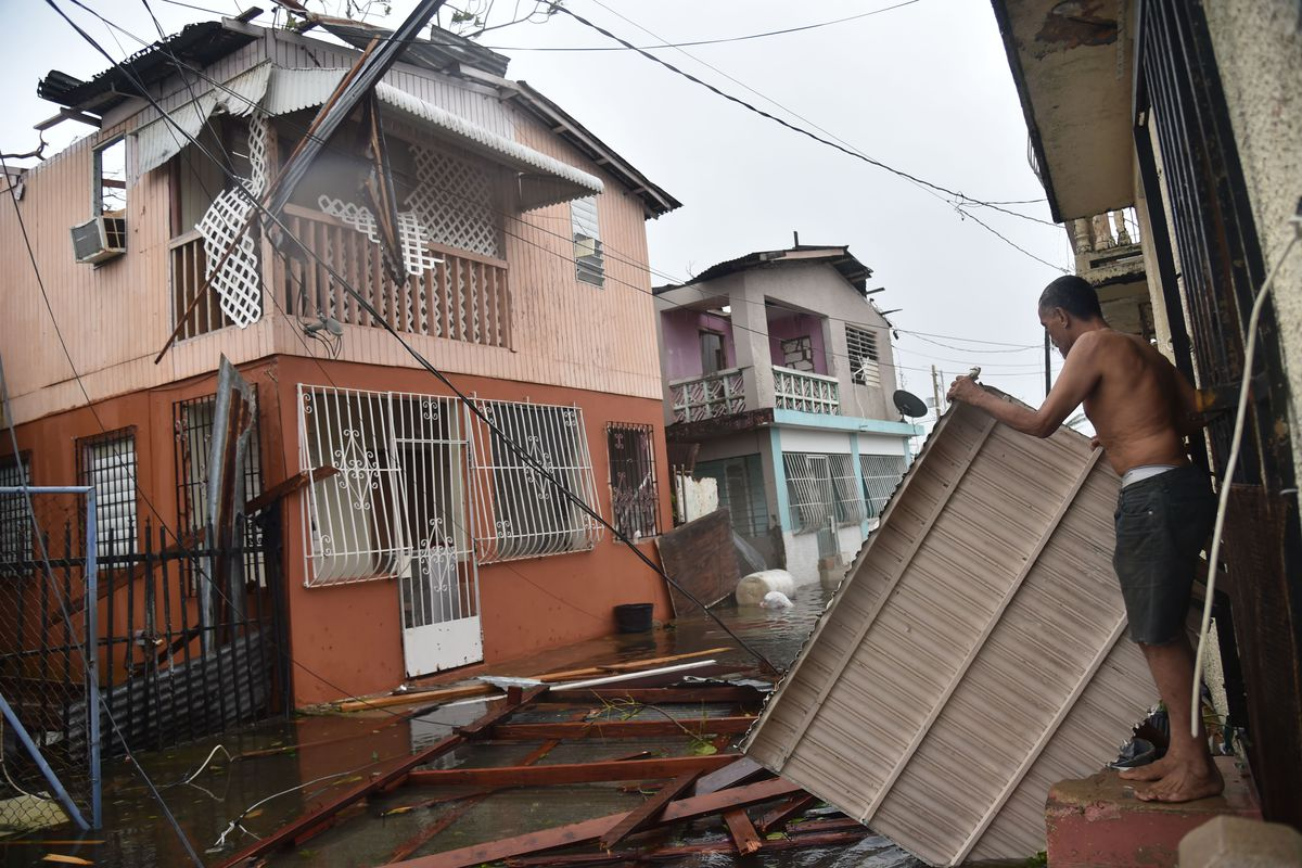A man stands on the doorstep holding a loose piece of sheet metal on a street damaged by a tropical hurricane.