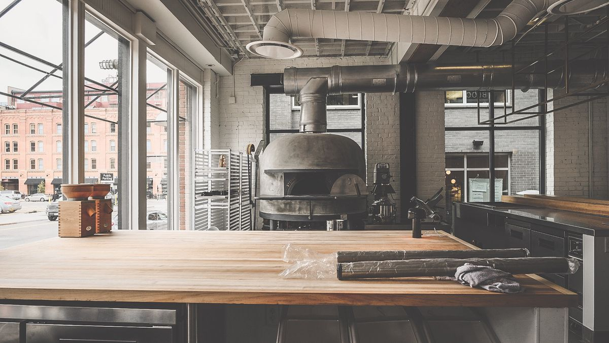 A photo looking into the kitchen at Brutø, with the Stefano Ferrara pizza oven visible behind a wood counter