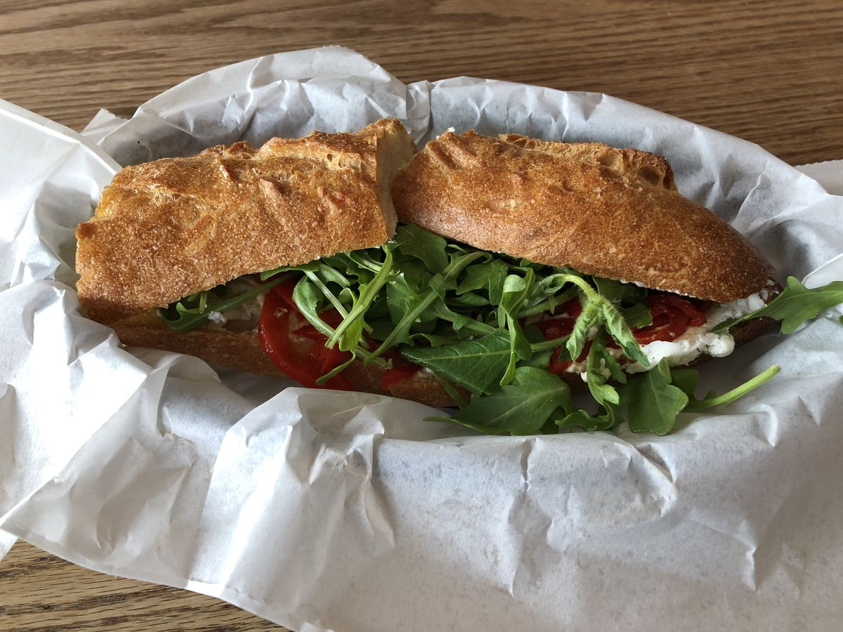A baguette sandwich with arugula, tomato, and cheese sits in a basket lined with white paper.
