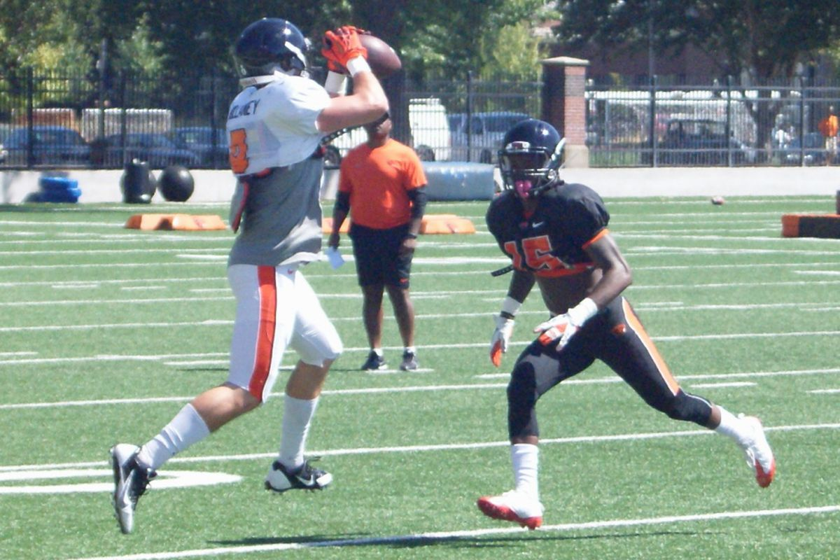 Richard Mullaney reels in a catch over Larry Scott in Oregon St.'s first full pad practice of the summer.