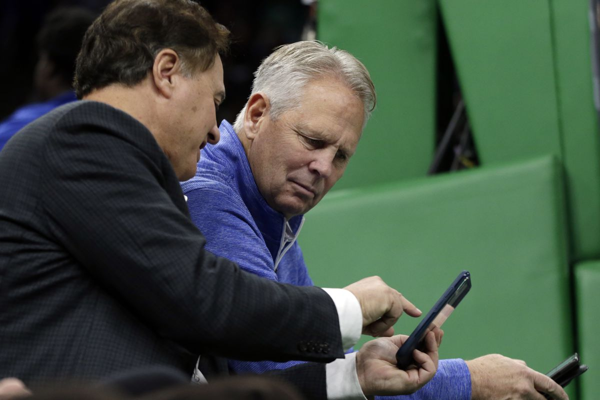 Boston Celtics owner Steve Pagliuca, left, shows something on his cellphone to Celtics President of Basketball Operations Danny Ainge during a break in the first quarter of an NBA basketball game against the Toronto Raptors, Friday, Nov. 16, 2018, in Bost