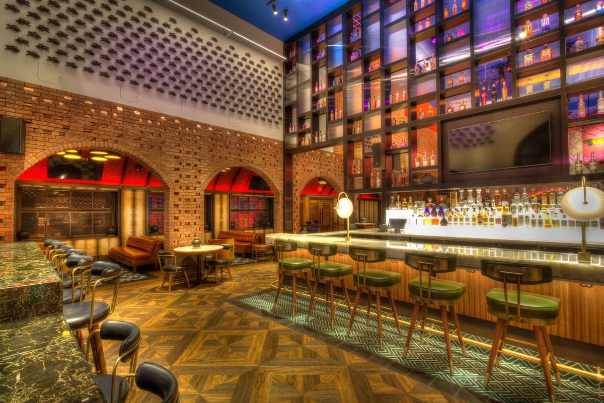 A bar scene with green high-top chairs and liquor housed in geometrical areas behind the bar