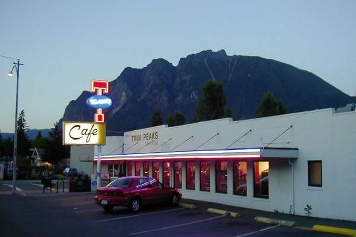 An exterior view of Twede's Cafe in North Bend, Washington, with the glowing neon sign and a mountain in the background