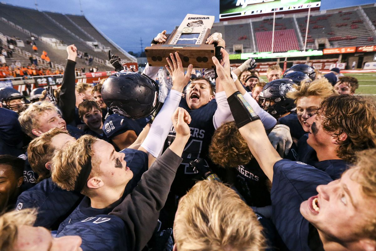 Corner Canyon's Jackson Light (74) hoists the state championship trophy after Corner Canyon rolled over American Fork 49-14 in the 6A state high school football game at Rice-Eccles Stadium in Salt Lake City on Friday, Nov. 22, 2019.