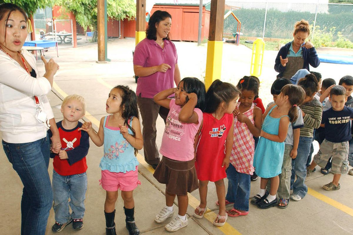Teacher Dany Chhy, left, leads a drill as preschoolers line up before lunch break at a Head Start Program in Hillsboro, Ore.