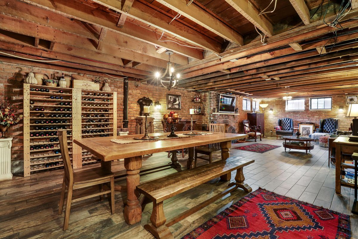 A long room with uncovered wood frame ceiling. There's a wine shelf next to a long wood table and benches. At the other end, there's leather chairs and couches around a fireplace.