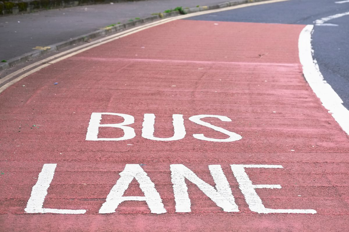 An photo of an asphalt road with one lane painted red and reading Bus Lane.