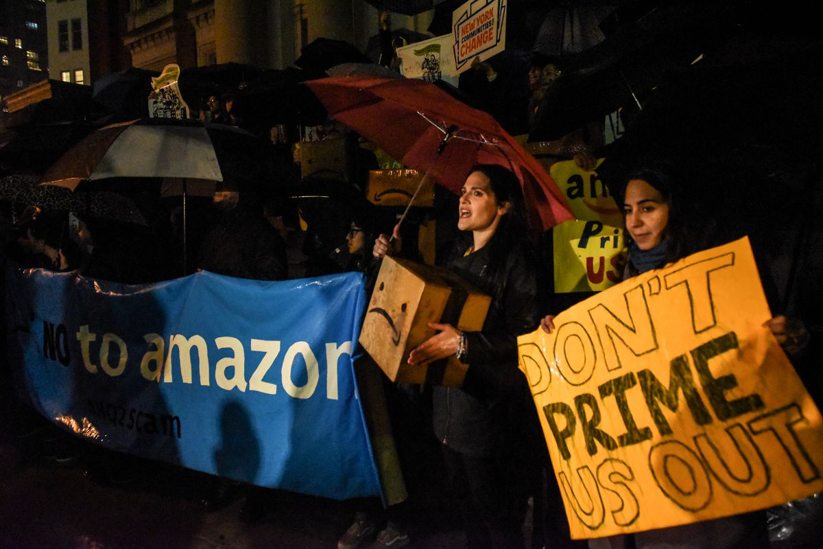 """People opposed to Amazon's plan to locate a HQ2 headquarters in New York City hold protest signs reading """"Don't Prime us out"""" and """"Say no to Amazon."""""""