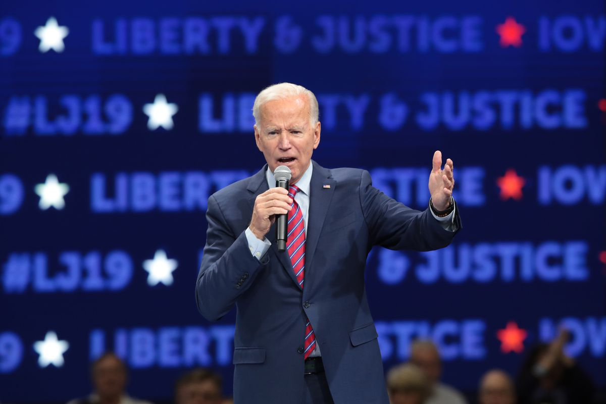 """Biden addresses a crowd in front of a screen reading """"Liberty and Justice."""""""