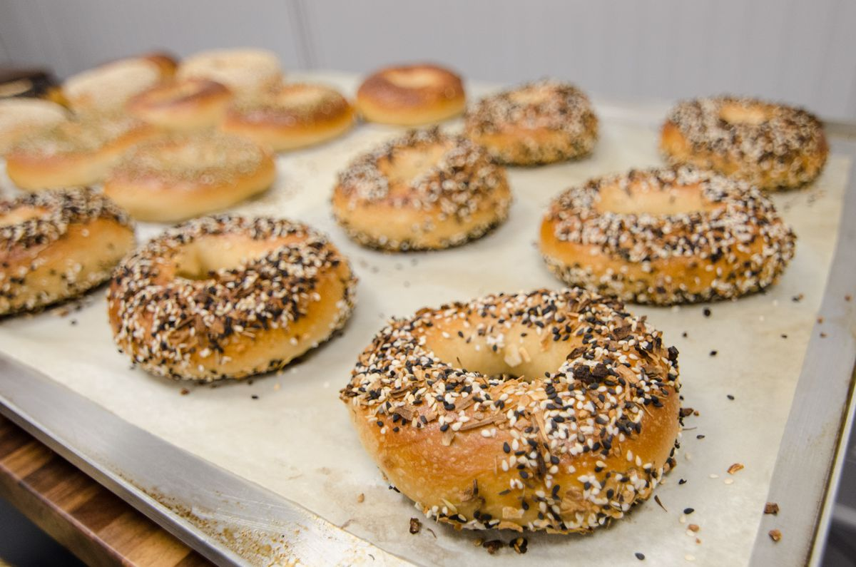 A tray of bagels, with everything bagels in the foreground