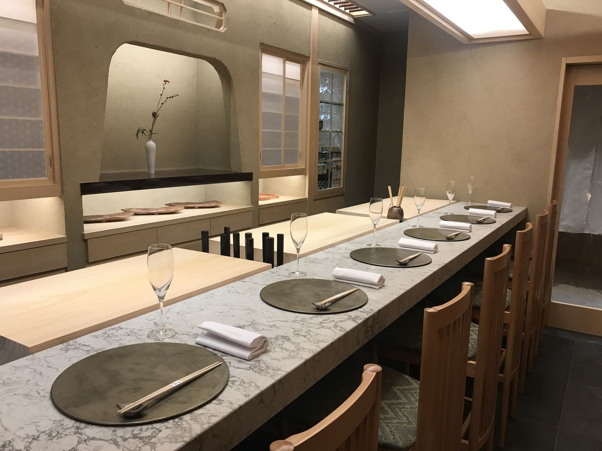 A marble-topped sushi bar with black round placemats