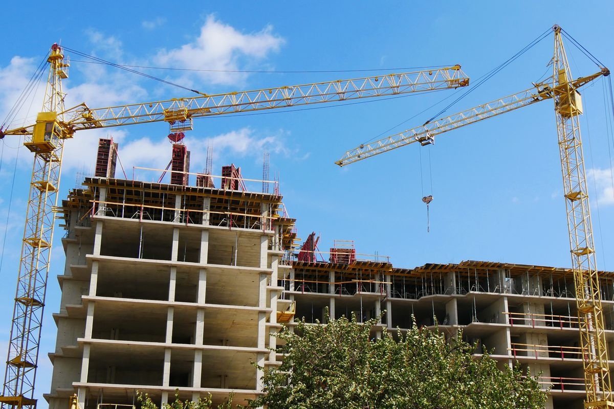Two cranes swing overhead at an apartment building construction site.