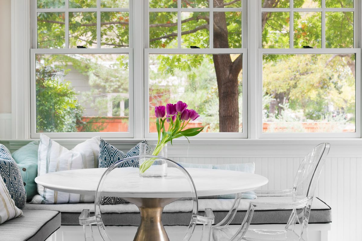 Three multipaned windows line a wall. There's a corder banquette with cushions behind a round table with Plexiglass chairs arranged around it. There's a vase with four casually arranged tulips on the table.