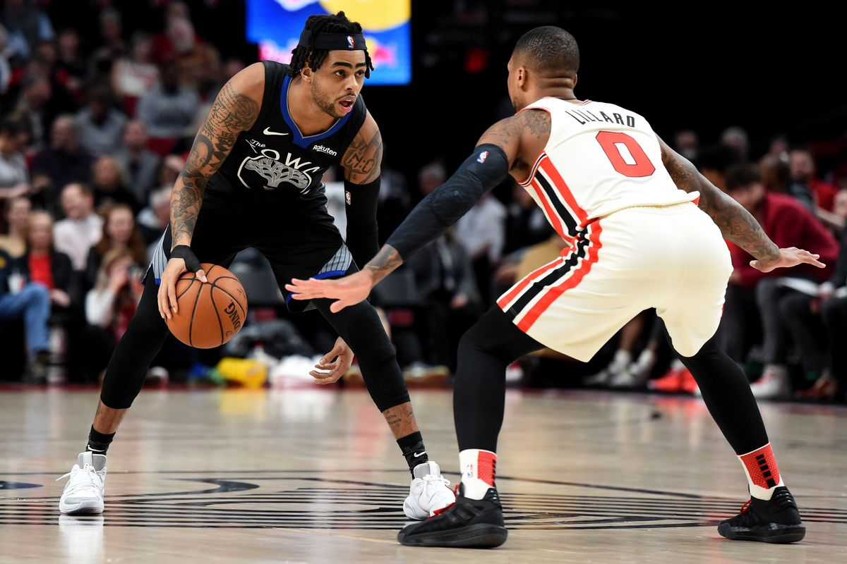 Golden State Warriors guard D'Angelo Russell dribbles the ball against Portland Trail Blazers guard Damian Lillard during the first half at Moda Center.