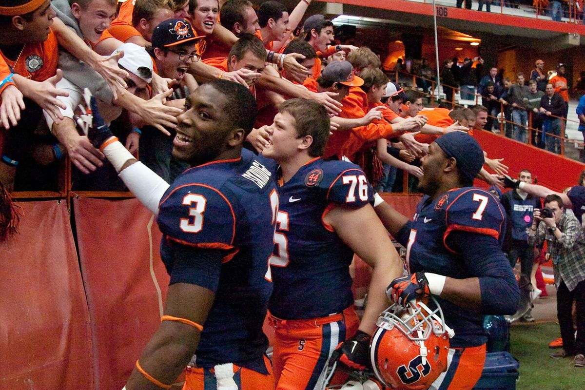 Syracuse Orange safety Durell Eskridge (3) , offensive lineman Jason Emerich (78) and linebacker Oliver Vigille (7) celebrate with fans after defeating the Louisville Cardinals in the Carrier Dome. Syracuse won the game 45-26.