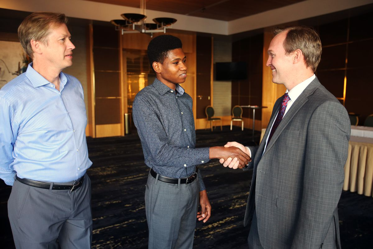 Getro Joseph, a young cellist from Haiti, meets Congressman Ben McAdams, right, who assisted Getro with his visa process. Utah Symphony cellist John Eckstein stands at the side at Abravanel Hall in Salt Lake City on Saturday, Dec. 7, 2019.