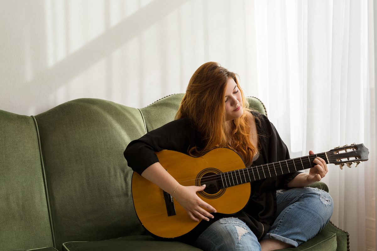 Mary Bolt plays the guitar on a green sofa.
